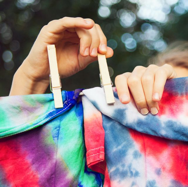 girl pinning tie dyed tshirts to clothes line
