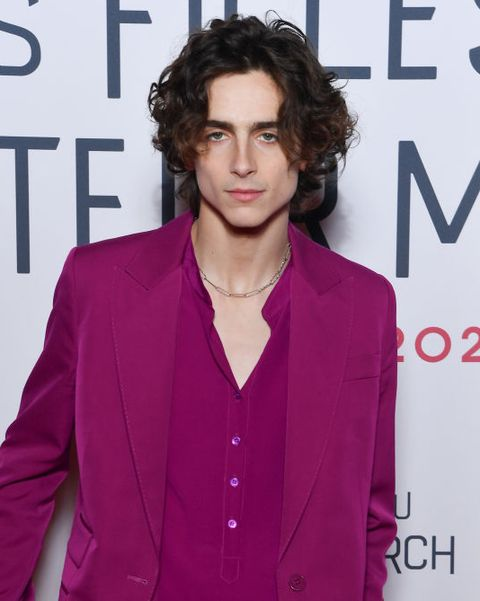 actor timothee chalamet wears a pink suit with a matching button up, paired with a silver chain necklace, on the red carpet