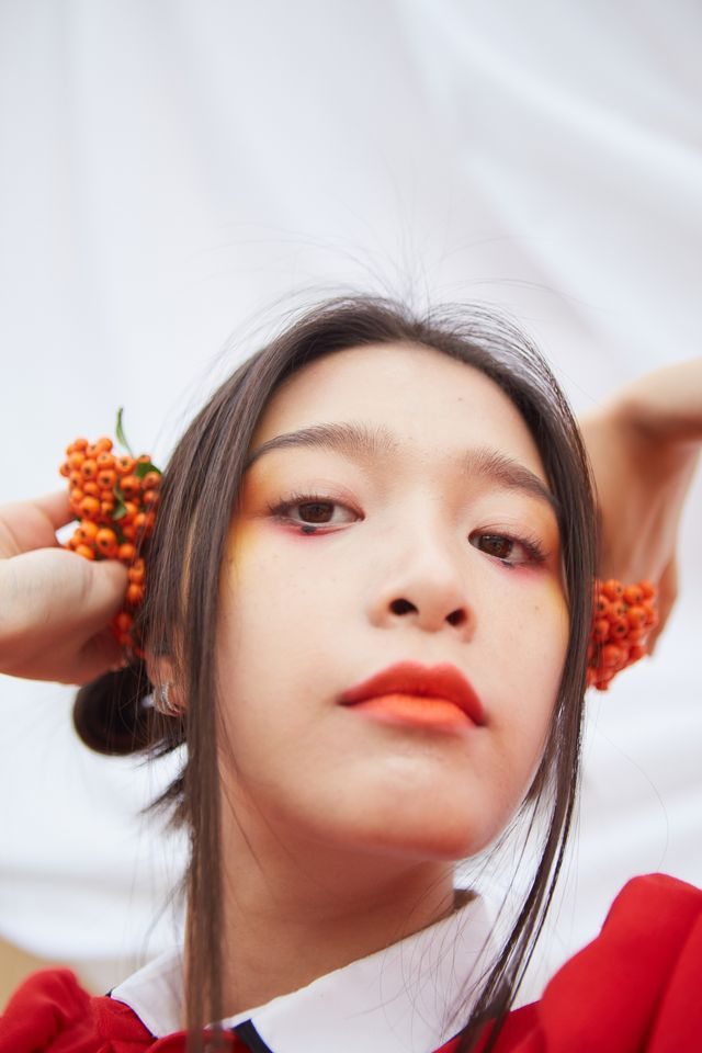 close up portrait of young beautiful asian woman with black hair wearing red dress with make up and red lips holding berries in her hands