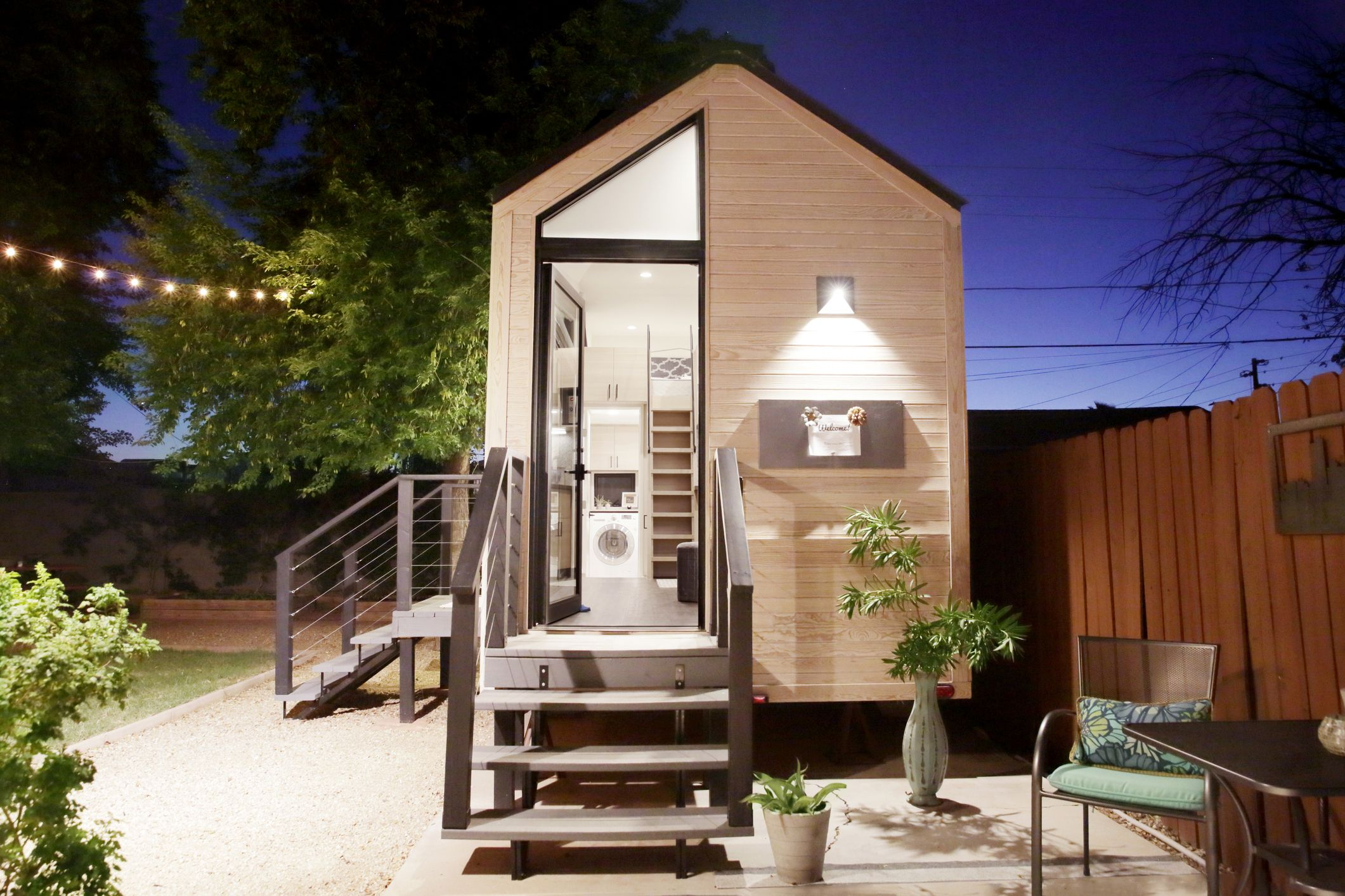 A Tiny House With Large Glass Windows, Sits In The Backyard At Night,  Surrounded