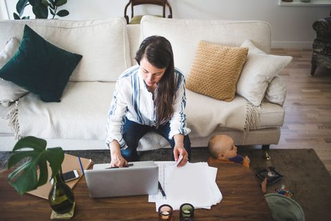 High angle view of female entrepreneur concentrating on work while daughter playing at home office