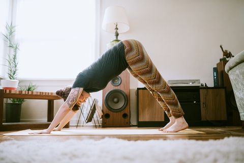 Young Adult Woman At Home Practicing Yoga