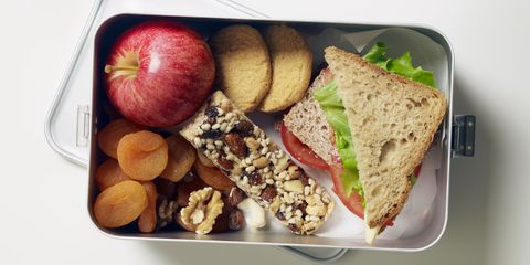 Gluten-free lunch box containing fruit, seed bar, biscuits and sandwiches