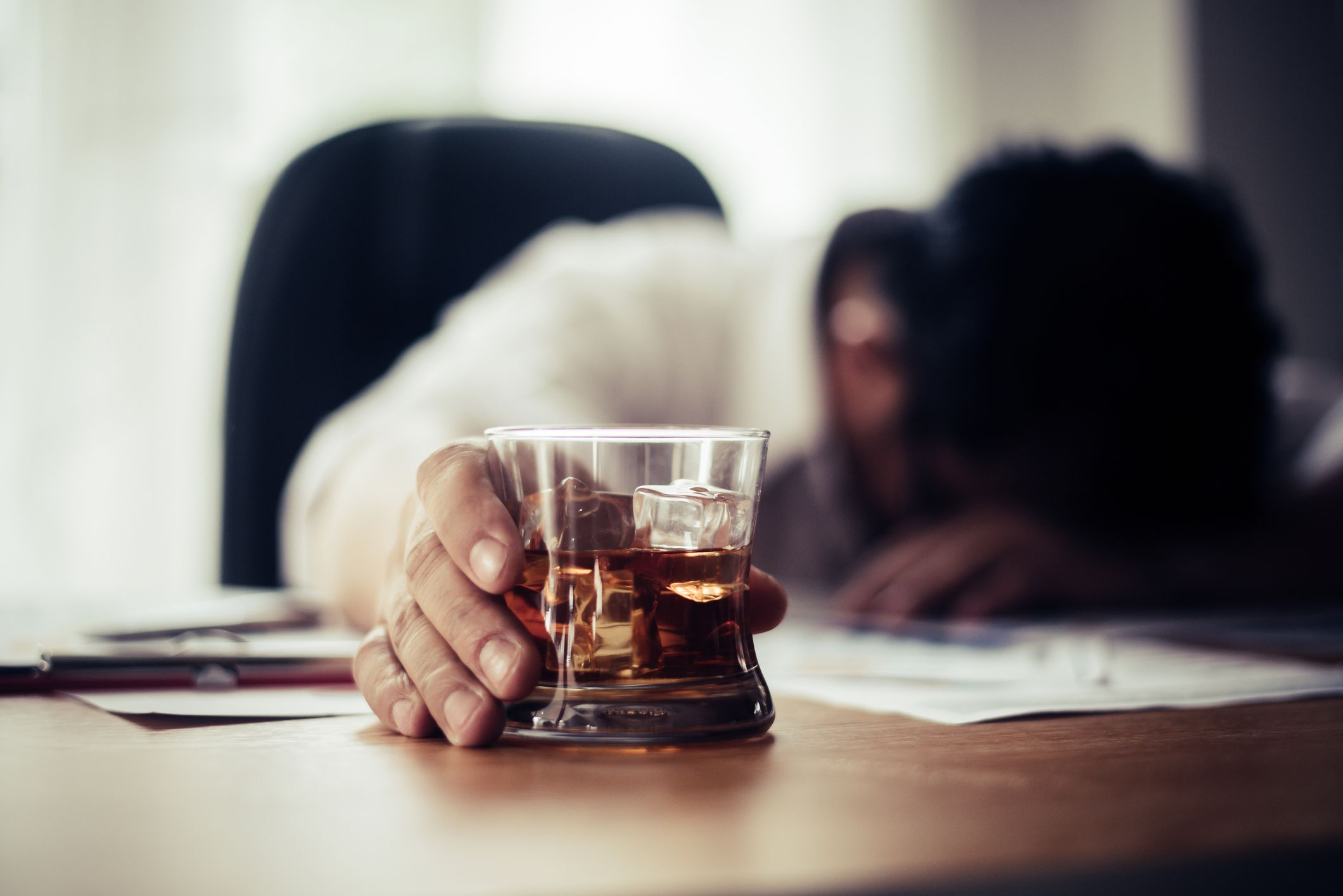 Tired Businessman Holding Whiskey Glass On Office Desk