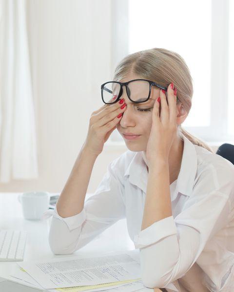 Tired businesswoman rubbing eyes in office
