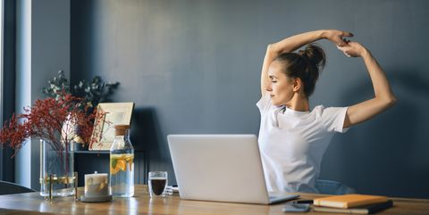 tired businesswoman stretching arms while sitting at desk in home office