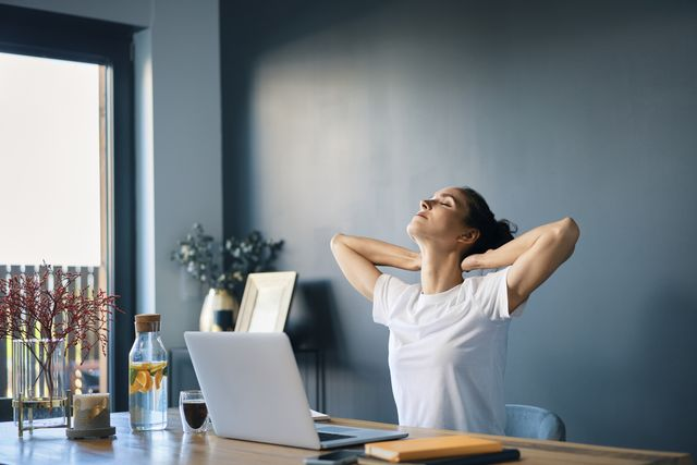 tired businesswoman with hands behind head sitting at desk in home office