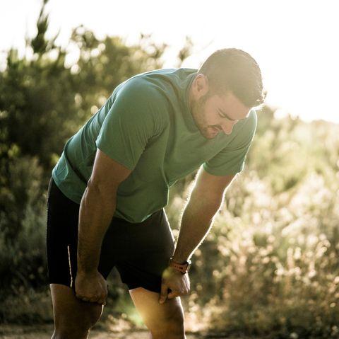 tired male runner bending in forest