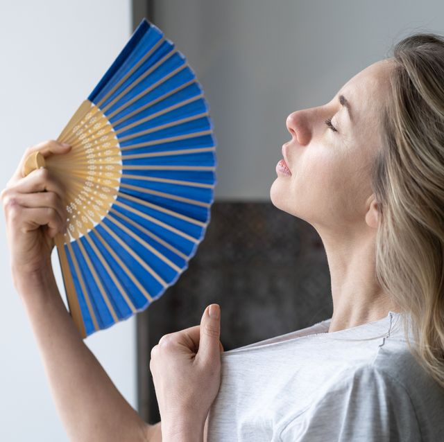 tired overheated woman using wave fan suffer from heat sweating, cools herself,  feels sluggish