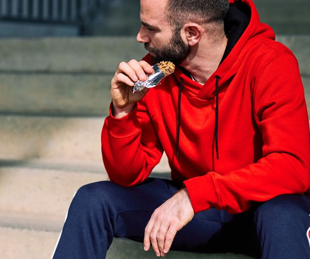 tired sportsman sitting on stairs outdoors and eating energy bar