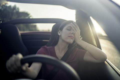 Tired woman driving car