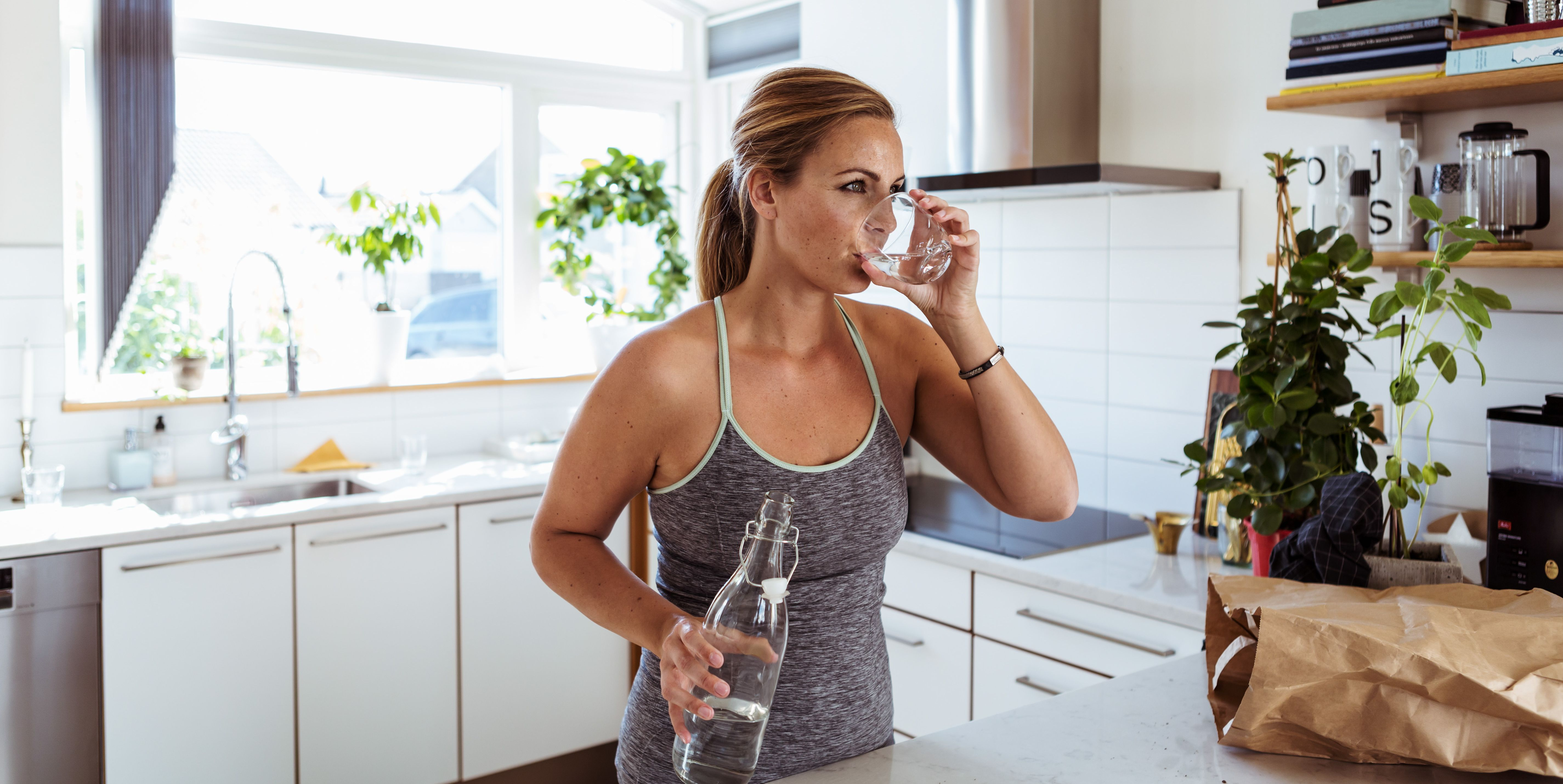 Tired woman in sports clothing drinking water while standing at kitchen