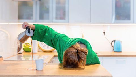 Vermoeide vrouw slaapt op keukentafel en giet koffie naast haar kopje
