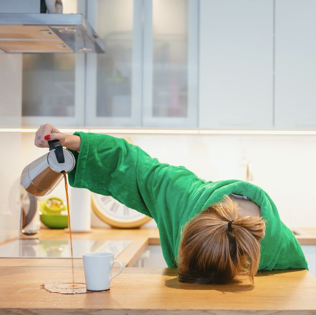 tired woman trying to drink morning coffee and sleeping on the table