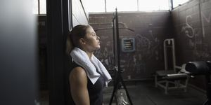 Tired woman weightlifting, resting with eyes closed at gym