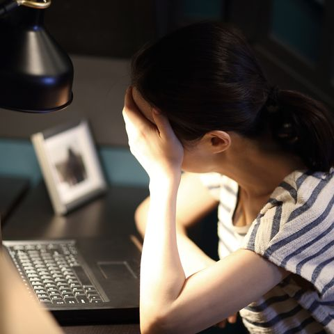 tired woman with head in hand on desk at home