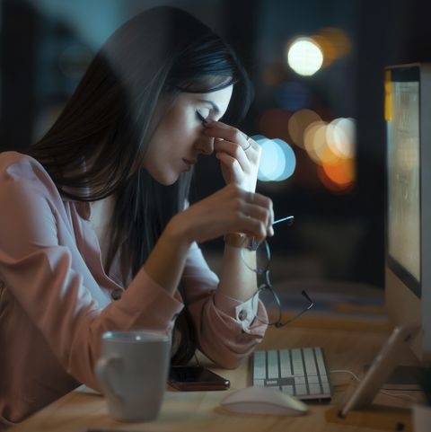 tired young woman with eyes closed sitting at desk in office