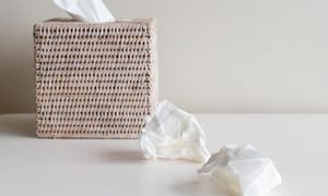 Tissue box and crumpled tissues on white table