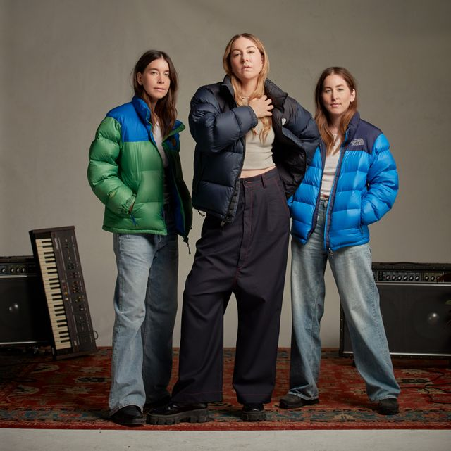 haim sisters wearing north face puffer jackets in blue, navy, and green