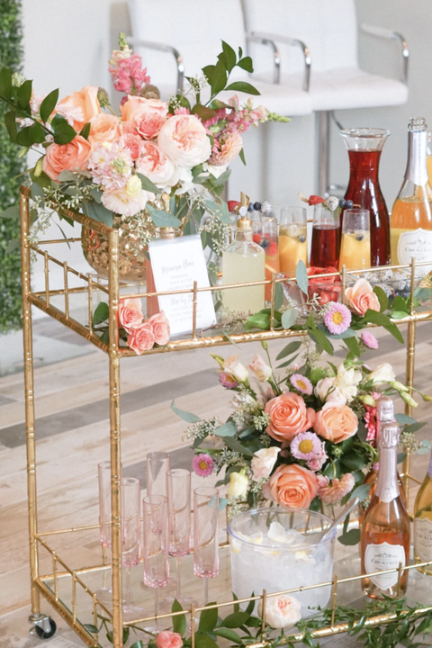 gold rectangle bar cart with coral roses and greenery on it along with juice, champagne, an ice bucket, and pink glasses