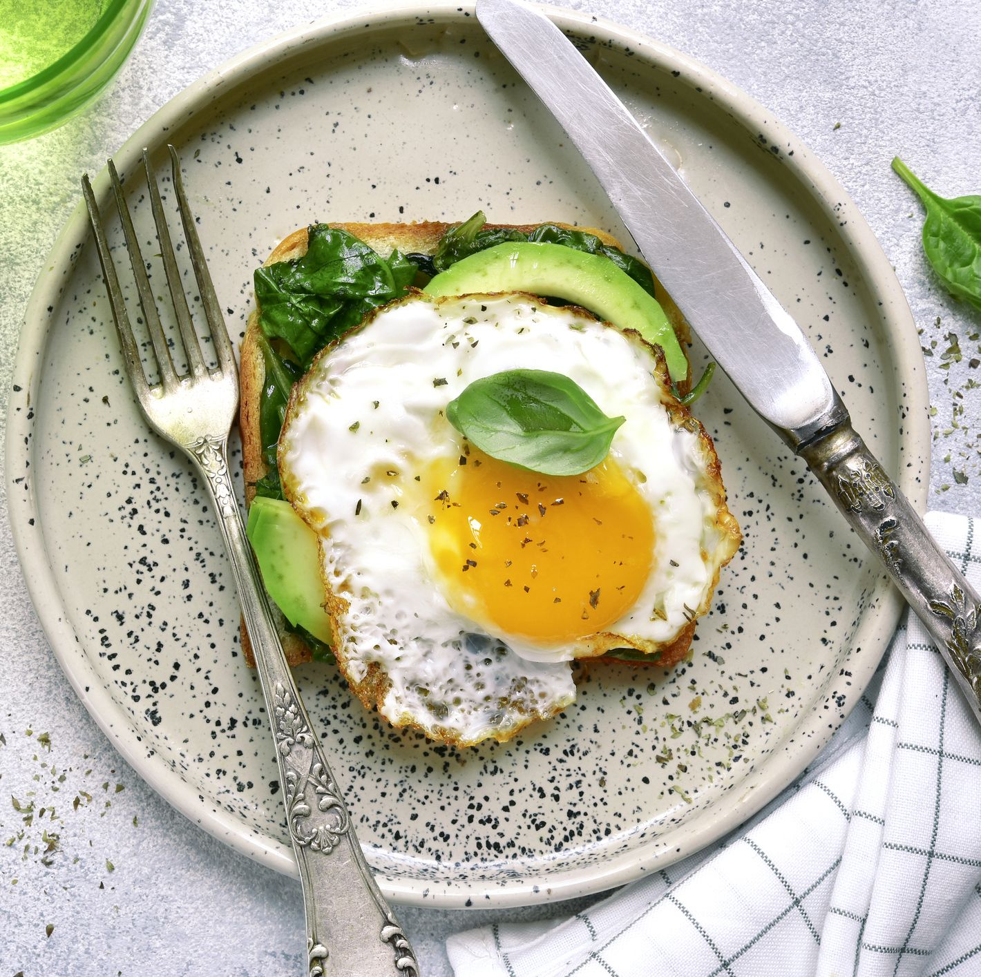 Toast with avocado slices, sauteed spinach and fried egg