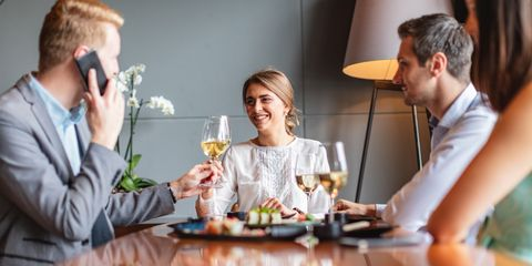 Toasting with colleague while talking on smartphone
