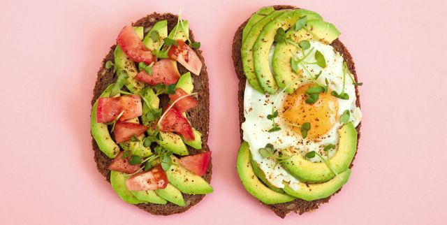toasts of dark bread with avocado slices, red tomatoes, fried egg and microgreen top view with pink background