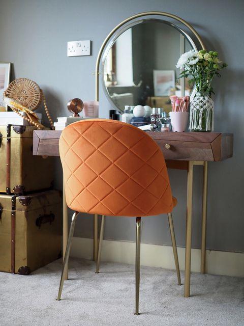 tocador mid century con espejo redondo y silla tapizada en terciopelo naranja