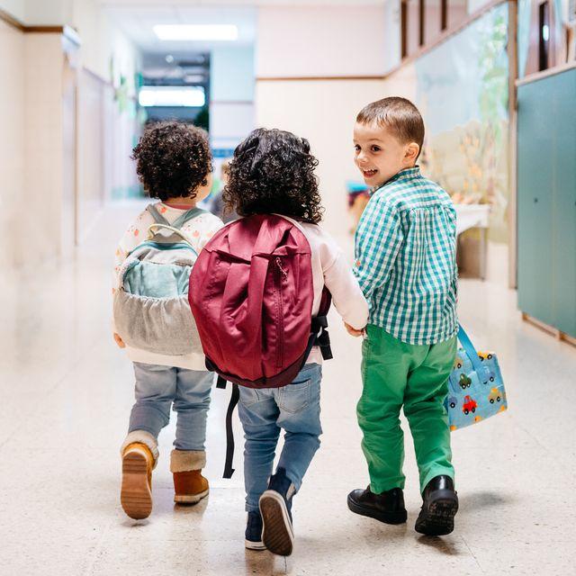 toddlers with backpacks walking down school hallway