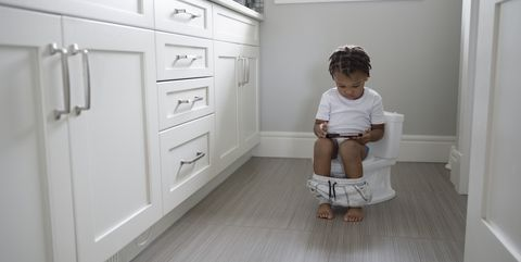 Toddler boy with smart phone potty training in bathroom