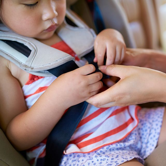 mom buckling toddler into car seat