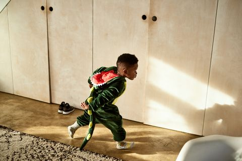 toddler running through house in dragon costume
