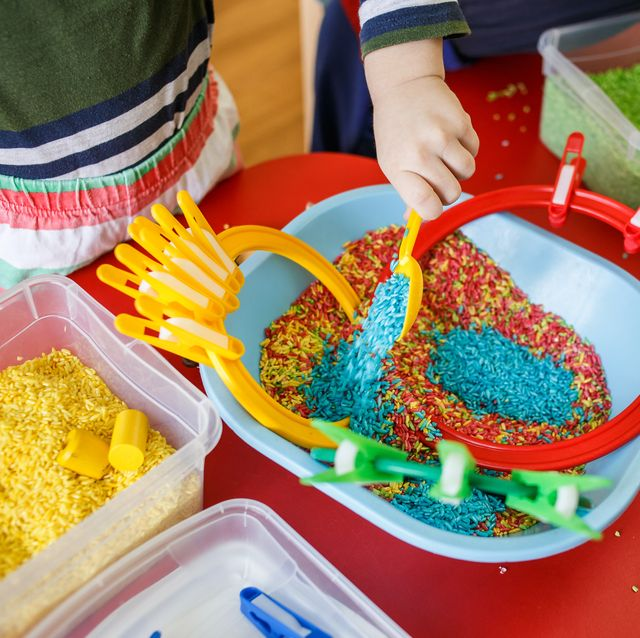 toddlers playing with sensory bin with colourful rice on red table