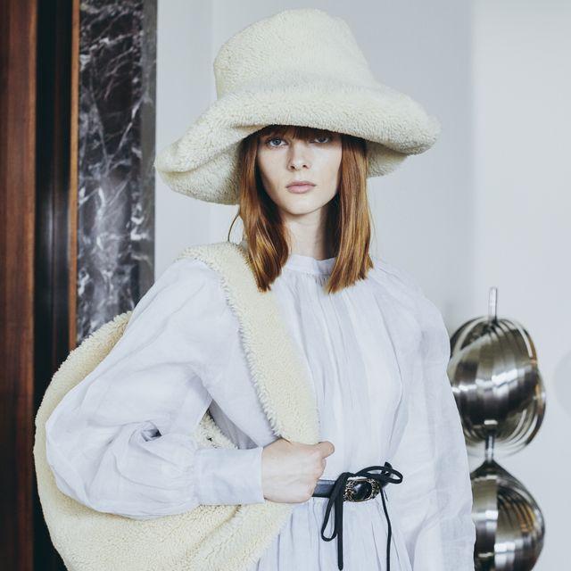 la modelo coco rocha en el backstage de tod's con sombrero y bolso en piel de borrego, vestido blanco y cinturón negro