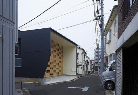 L'INGRESSO A CHECKERED HOUSE, IN UN QUARTIERE DENSAMENTE COSTRUITO DI TOKYO. LA FACCIATA SI CARATTERIZZA PER IL MOTIVO A SCACCHIERA DETERMINATO DALLA PARETE-LIBRERIA IDEATA DA TAKESHI SHIKAUCHI ARCHITECT OFFICE