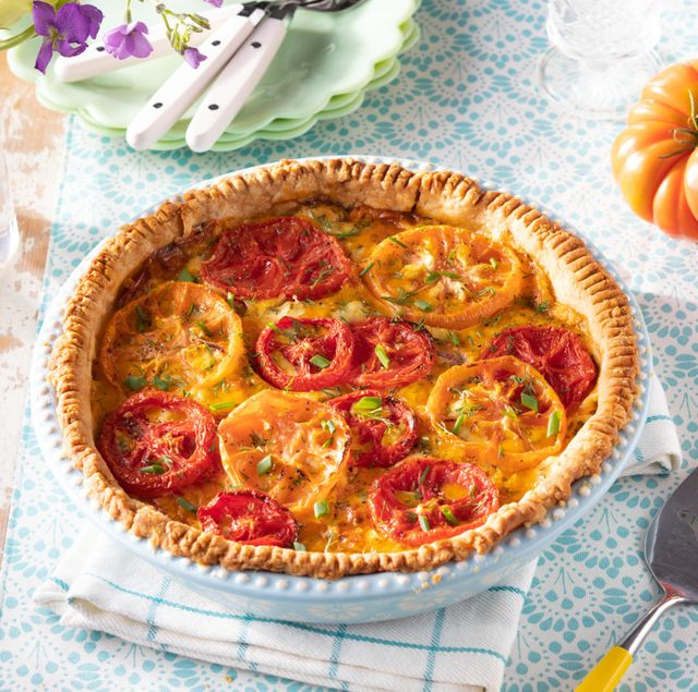 tomato pie with pie server and whole tomatoes