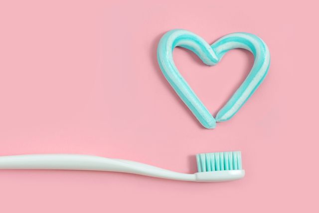 toothbrushes and turquoise color toothpaste in shape of heart on pink background dental and healthcare concept
