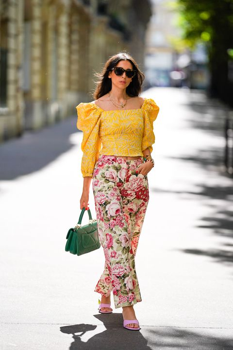 paris, france   june 15 street style photo session with gabriella berdugo wearing kenzo sunglasses, a yellow ruffled top with puff sleeves and shoulder pads from avavav, pink yuulie shoes, a green quilted chanel bag, pink floral print flared pants from parosh, a necklace, a watch, on june 15, 2020 in paris, france photo by edward berthelotgetty images