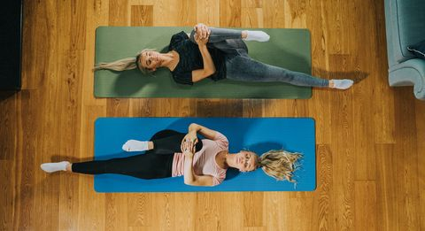 top down image of two woman on yoga mats holding their knee to their chest