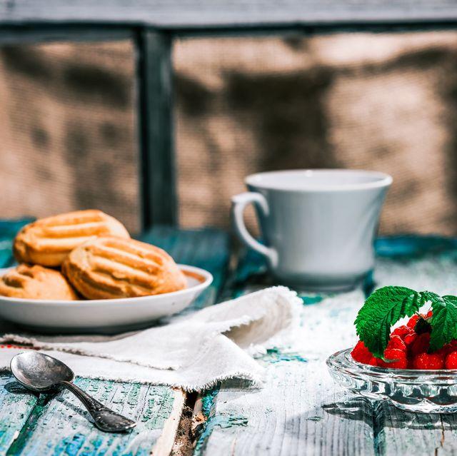 テーブルに置かれたマドレーヌとコーヒーカップ、木苺