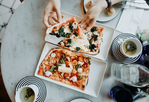 top shot of hands holding and enjoying freshly made pizza slices in the restaurant
