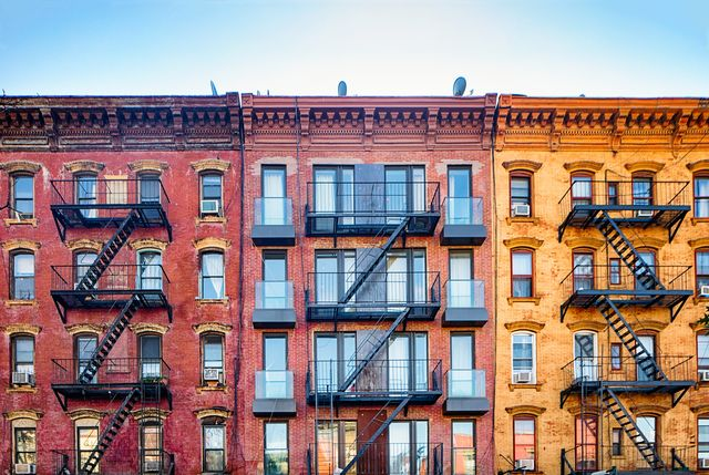 top stories of colorful williamsburg apartment buildings with steel fire escape stairways