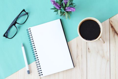 top view image of open notebook with blank pages and coffee cup on wooden background, ready for adding or mock up