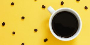 Top view of black coffee and beans on yellow background