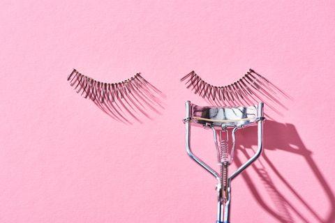 top view of false eyelashes and eyelash curler on pink background