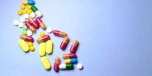 Top view of pharmaceutical medicine pills, tablets and capsules on blue background