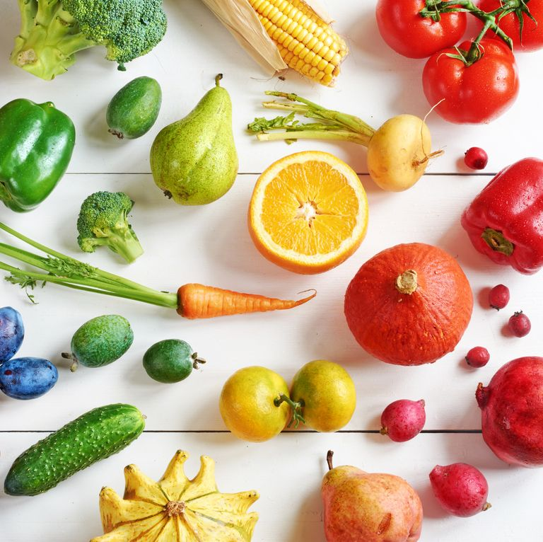 Top view of rainbow colored fruits and vegetables on a white table.