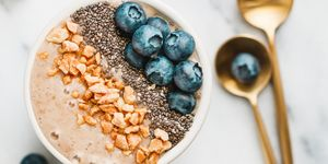 Top view of sa moothie bowl with fresh ripe blueberry, nuts, chia, banana and soya milk over white background. The concept of healthy eating and vegetarian food.