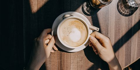 Top view of woman sitting by the window in coffee shop enjoying the warmth of sunlight and drinking coffee