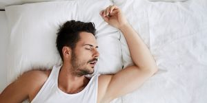 Top view of young attractive man sleeping with mouth open
